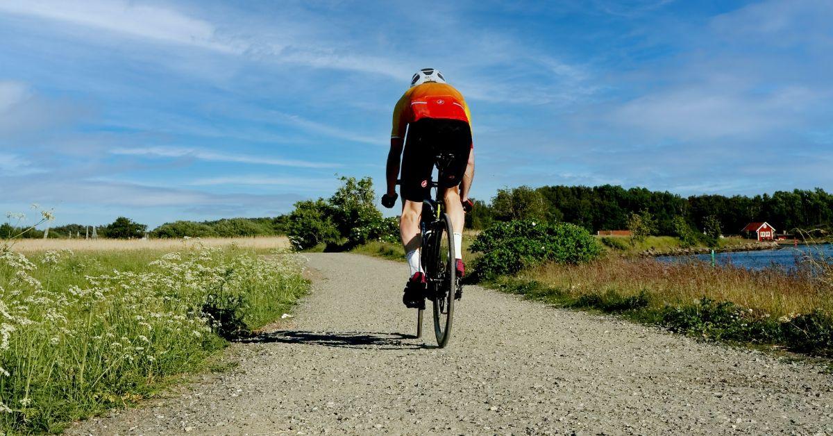 kolarz na rowerze szosowym na szutrowej drodze